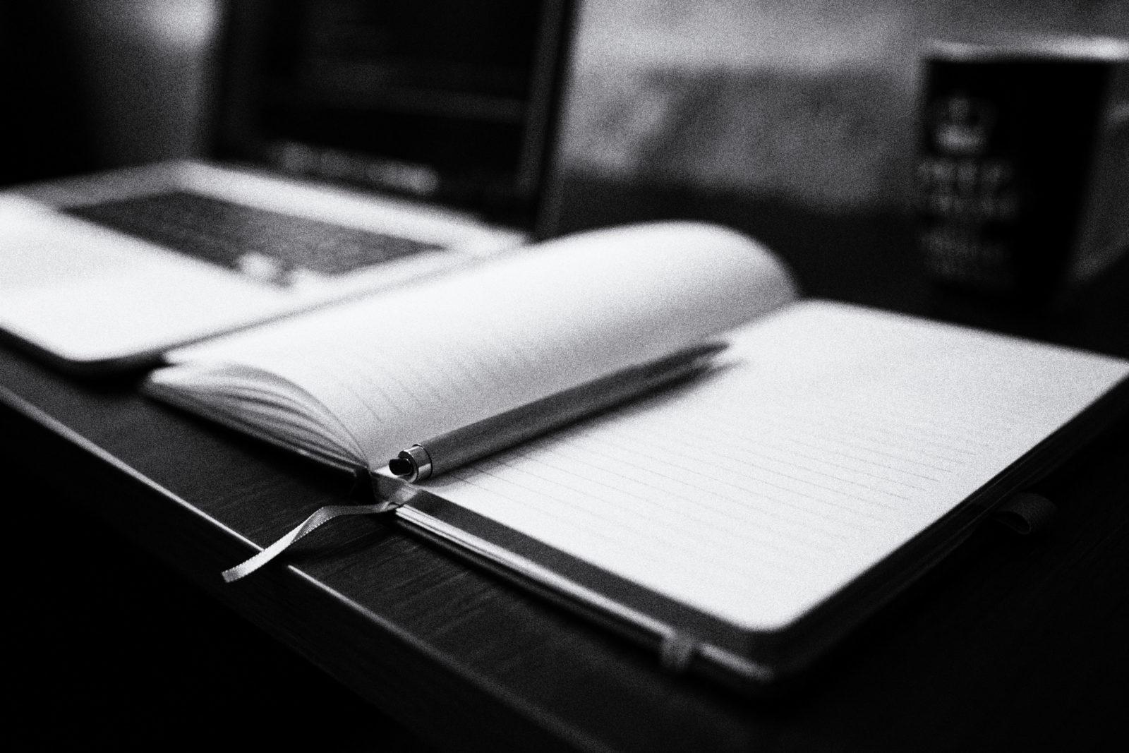 Bild eines Laptops und eines Notizblocks auf dem Schreibtisch in der Kanzlei